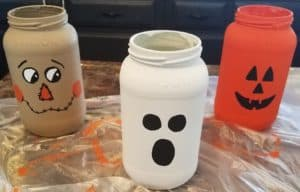 Cute mason jar Halloween decorations can be used as candle holders or a centerpiece. Click to see the full tutorial!